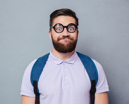 the ugly: Portrait of a male nerd with funny face over gray background Stock Photo