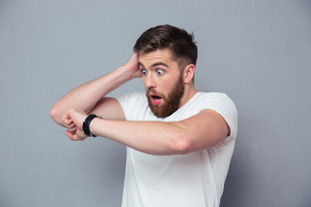 watch over: Portrait of a shocked man looking on wrist watch over gray background