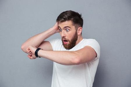 Portret van een geschokte man op zoek op horloge over grijze achtergrond Stockfoto