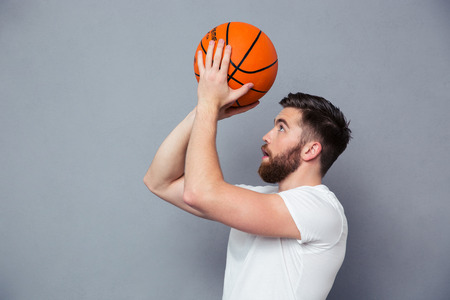 basket ball: Portrait of a young man reading to throw basket ball over gray background