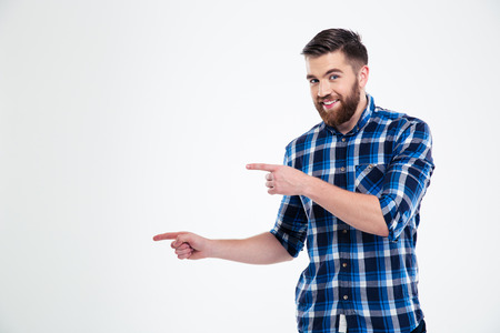 looking away from camera: Portrait of a happy casual man pointing fingers away isolated on a white background