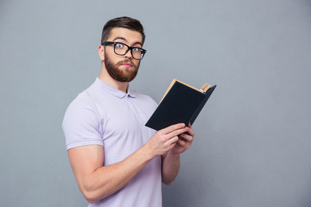 isolated on gray: Portrait of a serious hipster man holding book over gray background and looking at camera
