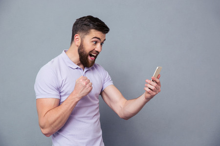 person looking: Portrait of a cheerful man using smartphone over gray background
