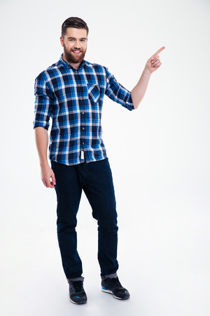 Full length portrait of a casual man pointing finger away isolated on a white background 스톡 콘텐츠
