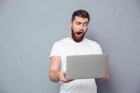 persona enferma: Retrato de un hombre con estúpido taza usando la computadora portátil sobre fondo gris