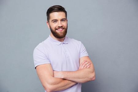 Portrait d'un homme décontracté heureux debout avec les bras croisés sur bakground gris et regardant la caméra