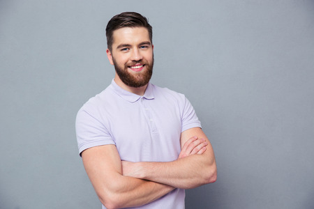 mani incrociate: Ritratto di un uomo casual felice in piedi con le braccia piegate su grigio bakground e guardando la fotocamera