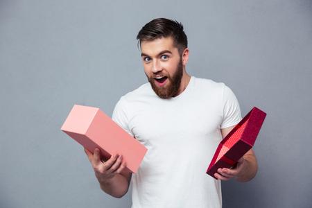 Portret van een jonge man opening geschenkdoos over grijze achtergrond