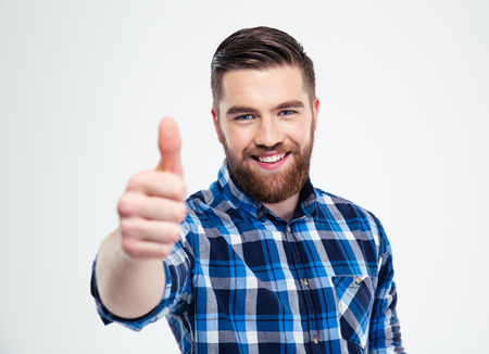 Portrait of a happy casual man showing thumb up isolated on a white background