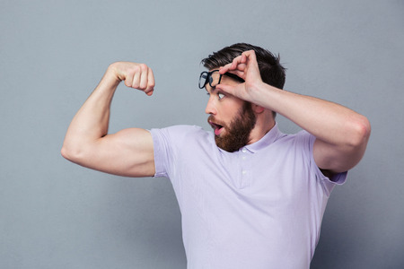 Potrait of a man looking at his biceps with delight over gray background
