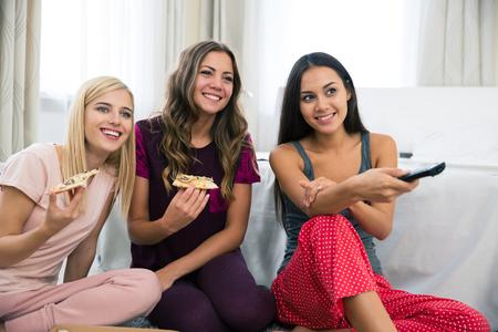 ver television: Retrato de una joven feliz tres amigas comiendo pizza y viendo la televisi�n en casa