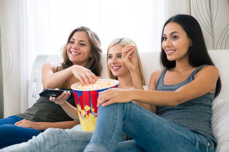 Portrait of a three happy girlfriends eating popcorn and watching tv at home