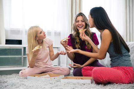 pizza: Retrato de un tres amigas felices comiendo pizza en casa