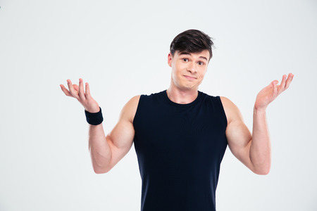 indecisive: Portrait of a fitness man shrugging shoulders isolated on a white background