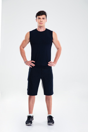 ropa deportiva: Retrato de cuerpo entero de un hombre guapo en ropa deportiva de pie aislado en un fondo blanco y mirando a la cámara