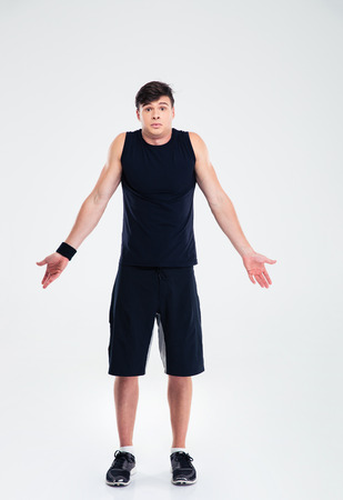 indecisive: Full length portrait of a sports man shrugging shoulder isolated on a white background