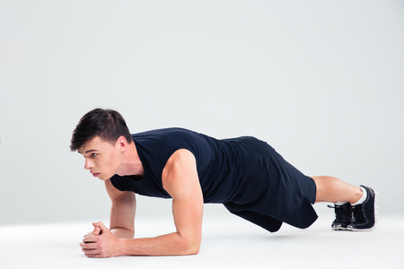 leaning on elbows: Portrait of a sports man doing elbow plank exercises isolated on a white background Stock Photo