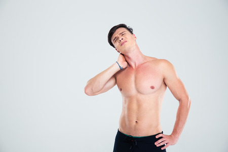 at close quarters: Portrait of a handsome man having neck pain isolated on a white background