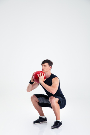 workout: Full length portrait of sports man workout with fitness ball isolated on a white background