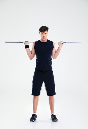 well build: Full length portrait of a young fitness man workout with barbell isolated on a white background Stock Photo