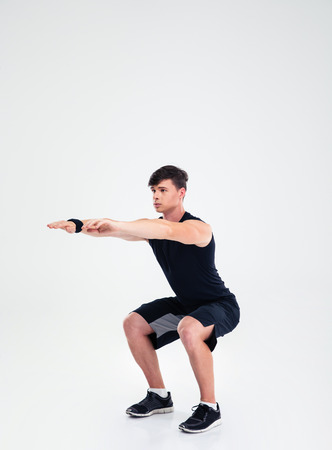 en cuclillas: Retrato de cuerpo entero de un hombre de la aptitud que hace ejercicios en cuclillas aislado en un fondo blanco