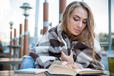Portrait of attractive young woman reading book in cafe Stock Photo
