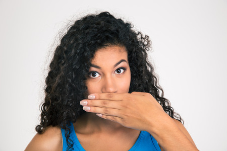 hands in mouth: Portrait of a afro american woman covering her mouth isolated on a white background