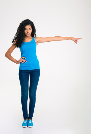 pretty black woman: Full length portrait of a serious afro american woman pointing finger away isolated on a white background