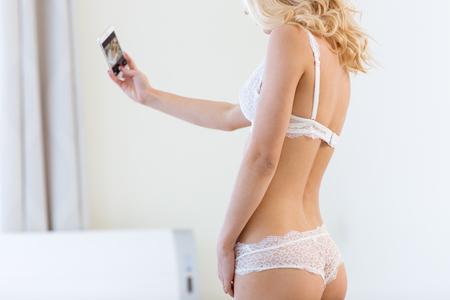 sexy young girls: Портрет сексуальная женщина в белье решений selfie фото на смартфоне дома Фото со стока