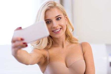 donna sexy: Ritratto di una ragazza sorridente nel processo lingerie selfie foto su smartphone a casa
