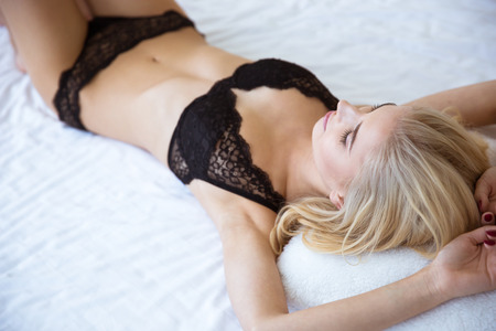 nackte schwarze frau: Porträt einer schönen sexy Frau in Dessous auf dem Bett liegend