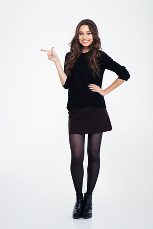 Full length portrait of a smiling girl pointing finger away isolated on a white background