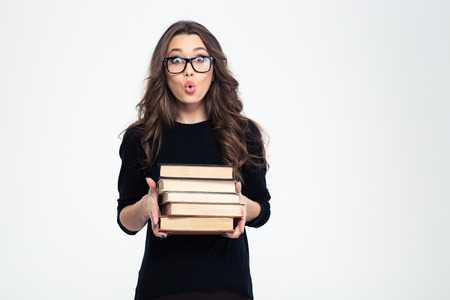 Portrait of amazed woman in glasses holding books and looking at camera isolated on a white background Standard-Bild
