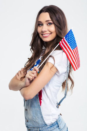 Portrait of a smiling cute woman holding USA flag isolated on a white background