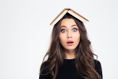 female head: Retrato de una mujer joven con el libro en la cabeza mirando a la cámara aislada en un fondo blanco Foto de archivo