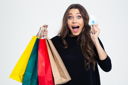 happy shopper: Portrait of a cheerful woman holding shopping bags and bank card isolated on a white background