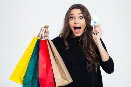 Portret van een vrolijke vrouw met boodschappentassen en bankkaart die op een witte achtergrond