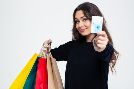 Portret van een gelukkige jonge vrouw met boodschappentassen en bankkaart die op een witte achtergrond