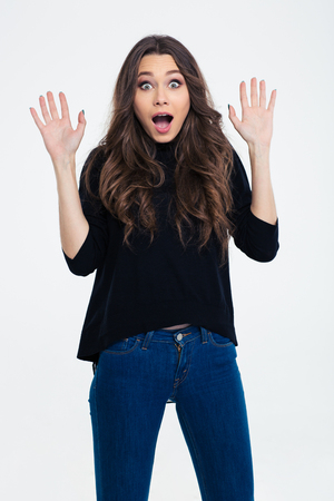 Portrait of a happy amazed woman standing with raised hands isolated on a white background