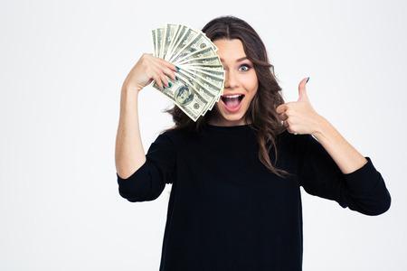 signos de pesos: Retrato de una niña alegre que cubre su ojo con billetes de dólares y que muestra el pulgar arriba aislados en un fondo blanco