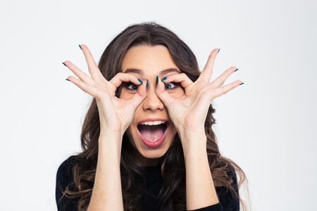 Portrait of a funny young girl looking at camera through fingers isolated on a white background