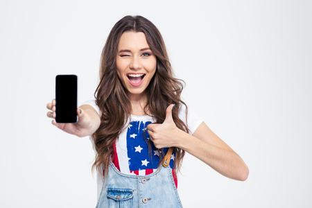 Portrait of a cheerful woman showing blank smartphone screen and showing thumb up isolated on a white background