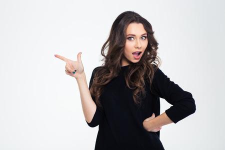Portret van een mooie vrouw wijzende vinger weg geïsoleerd op een witte achtergrond Stockfoto