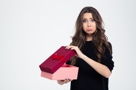 dissatisfied: Portrait of a sad woman standing with opened gift box isolated on a white background and looking at camera Stock Photo