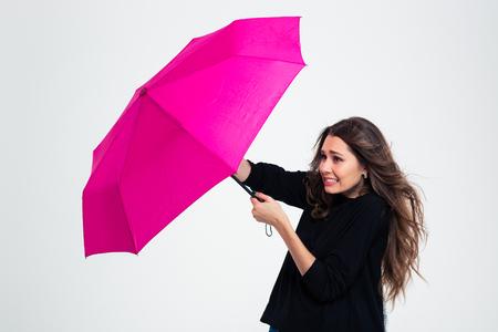 Portret van een jonge vrouw met paraplu in een sterke wind die op een witte achtergrond