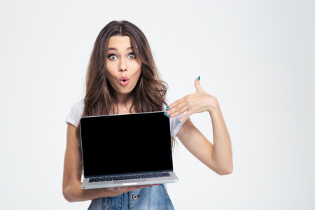 dedo señalando: Retrato de una mujer que señala el dedo feliz en pantalla de la computadora portátil en blanco aislado en un fondo blanco