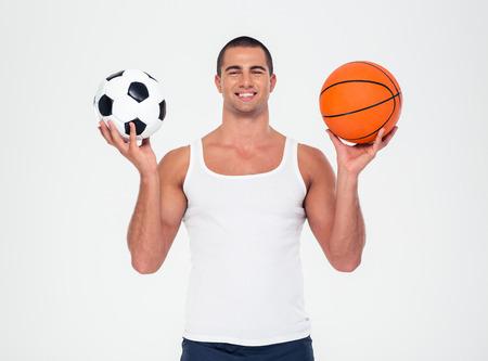 balon de futbol: Retrato de un fútbol y baloncesto bola hombre sonriente sosteniendo aislado en un fondo blanco Foto de archivo