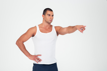 finger pointing: Portrait of a serious muscular man pointing finger away on something isolated on a white background