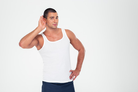 something athletic: Portrait of athletic man holding his hand near his ear to listening something isolated on a white background Stock Photo