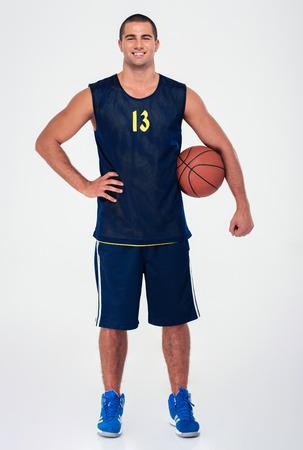 hombres guapos: Retrato de cuerpo entero de un jugador de baloncesto y guapo de pie aislado en un fondo blanco y mirando a la c�mara